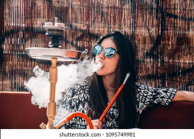 Awesome girl enjoying shesha outside on a sunny day
