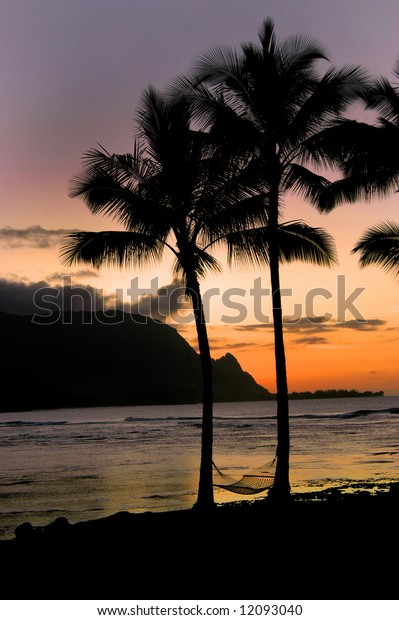 Awesome Kauai sleeps for another night.  Sunset in orange and purple.  Palm trees silhouetted.