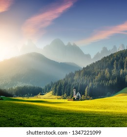 Awesome landscape with colorful sky over the Dolomites mountains. Fantastic View on mountain valley under sunlight and famouse church in santa Maddalena village during sunrise. creative image