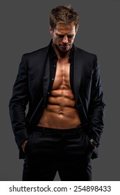 Awesome male in black suit dressed on naked torso. Isolated on grey
