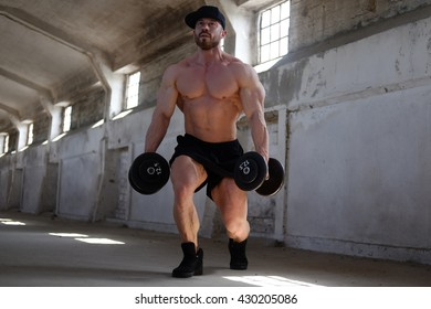 Awesome male bodybuilder in black cap and shorts exercising with dumbbells in a warehouse.