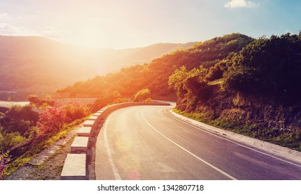 Awesome natural scenery. Beautiful winding mountain road with a perfect asphalt with high rocks and with bright sky in summer  in sunrise time.