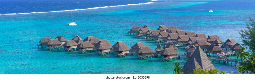Awesome oceanfront hotel resort resting above the calm emerald colored ocean on a sunny summer day. Beautiful view of luxury overwater villas and sailboat in the middle of breathtaking tropical sea.