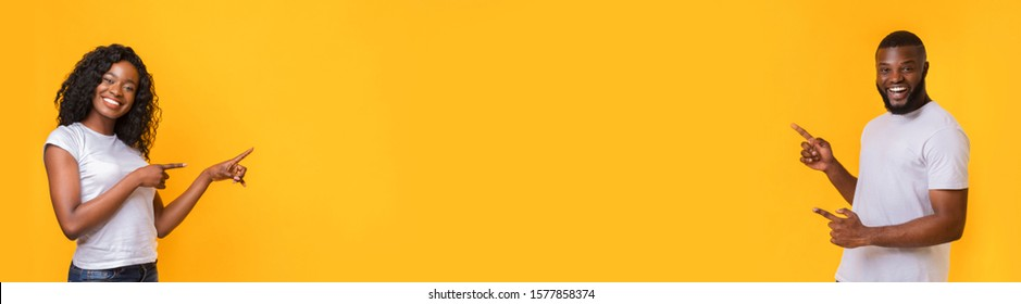 Awesome offer. Millennial african american couple pointing at empty space yellow background, panorama