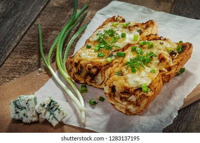 Awesome open face grilled cheese sandwiches made of baguette, mozzarella, gorgonzola, green onion on a rustic table.