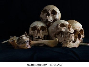 Awesome pile of skull and bone on black cloth and black background, Still Life style, selective focus