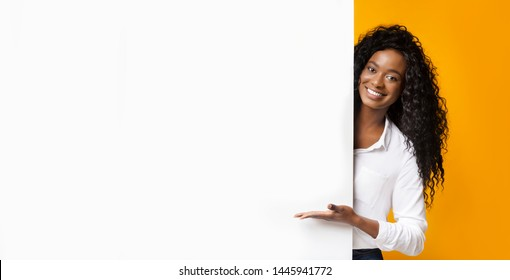 Awesome promo. Smiling african american woman presenting something on white blank board with empty space, panorama