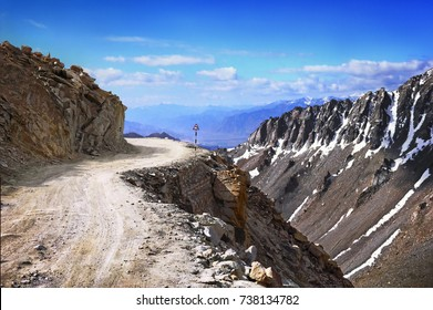 Awesome scenic view, high mountain country road with street sign in steep rugged cliff at the background of cloudy blue sky, Leh, Ladakh range, Himalayas, Jammu & Kashmir, Northern India, Central Asia