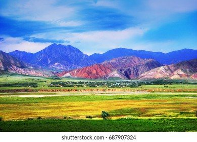 Awesome scenic view, kyrgyz village in a green valley surrounded with distant colorful mountain range under cloudy blue sky at evening time, Tien Shan, Bishkek - Osh highway, Kyrgyzstan, Central Asia