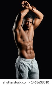awesome sportsman with raised arms in white pants showing his ideal, perfect abs, body. sporty life, hobby, wellness