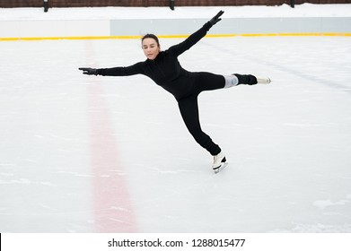awesome stylish young woman doing figure skating elements on the open ice rink. Winter fun activity and healthy life style. Champion's training hard.