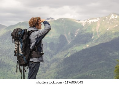 awesome touris is standing on the peack of the mountain and enjoying the breathtaking scenery. copyspace. extreme sport concept