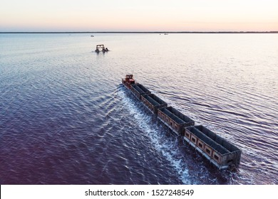 Awesome train rides on the rail in the water with white salt on the background of beautiful blue sky. aerial view, view from the top
