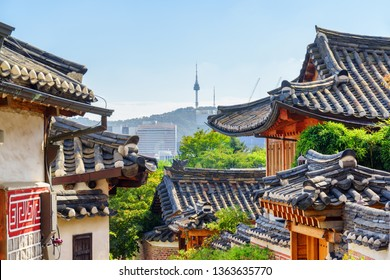 Awesome view of black tile roofs of traditional Korean houses at Bukchon Hanok Village in Seoul, South Korea. Amazing architecture. Seoul Tower on Namsan Mountain is visible on blue sky background.