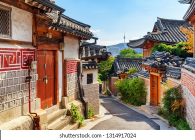 Awesome view of cozy old narrow street and traditional Korean houses of Bukchon Hanok Village in Seoul, South Korea. Seoul Tower on Namsan Mountain is visible on blue sky background. Scenic cityscape.
