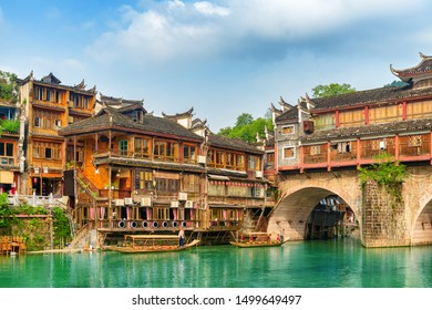 Awesome view of the Hong Bridge (Rainbow Bridge) over the Tuojiang River (Tuo Jiang River) and old traditional Chinese wooden riverside houses in Phoenix Ancient Town (Fenghuang County), China.