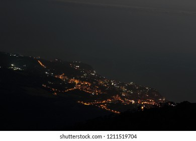 Awesome view from Mount Ai-Petri on the night resort city of Yalta, Crimea, Russia. Cityscape with night city lights on the coast of the Black Sea.