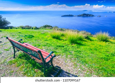 Awesome view from red wooden bench to the coastline sea bay with crystal clear azure water, distant islands in the calm warm sea. Beautiful summer seascape. Agios Stefanos cape. Afionas. Corfu. Greece