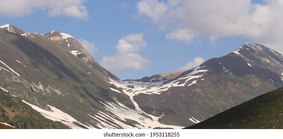 Awesome view of snow present on high mountains with clouds in the sky in the daytime at a picnic spot.