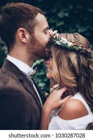 Awesome wedding couple. Groom kissing pretty bride.