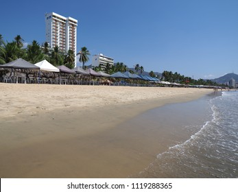 Awesome white hotel and umbrellas on sandy beach at bay of mexican Acapulco city landscapes and waves of Pacific Ocean in Mexico, clear blue sky in 2018 hot sunny winter day, North America on March