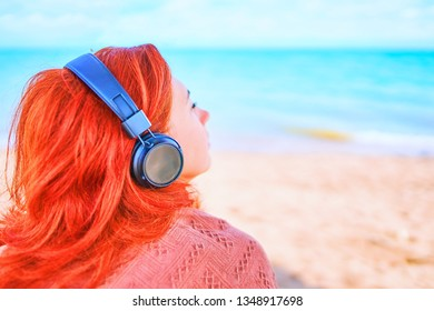 Awesome woman listening to music on the beach. The girl enjoys a beautiful view of the sea and listens to songs.
