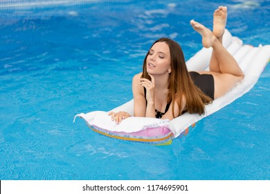 awesome woman with long. dark hair is lying on the air bed in the swimming pool.side view photo.rest, free time, enjoyment concept. holiday-maker swimming on the mattress