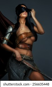 Awesome woman in Roman armor and sword. Isolated on grey.