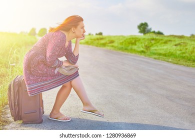 Awesome woman in summer dress and hat hitchhiking with suitcase on the road at spring. Female sitting on Luggage waiting for transport. Travel concept