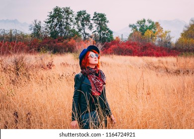 Awesome woman is walking in the park in cloudy weather at autumn. Red-haired female in a blue hat, coat and sunglasses walks the field at fall looking to the sky
