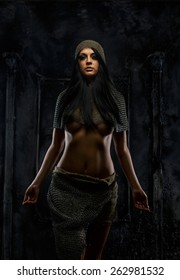 Awesome young woman in ancient armor on grey background.