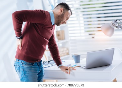 Awful backache. Young emotional exhausted worker of a big company leaning towards the table while suffering from an awful backache and wishing to go home