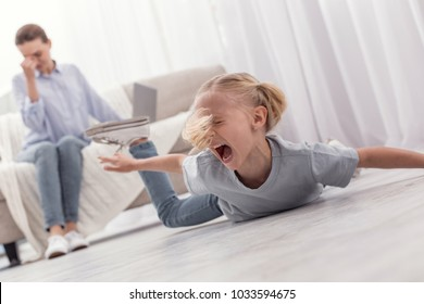 Awful behavior. Mischievous little blond girl shouting while lying on floor and demanding toy