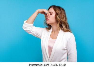 Awful smell! Portrait of woman with wavy hair in white jacket pinching her nose, expressing disgust to unpleasant odor, fart gases, her eyes closed with abhor. studio shot isolated on blue background