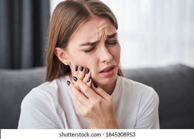 Awful toothache. Frustrated young women suffering from toothache while sitting on the sofa at home. Stock photo. Health and illness concept