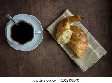 Awhite platter of croissants on wooden table with a cup of coffee.