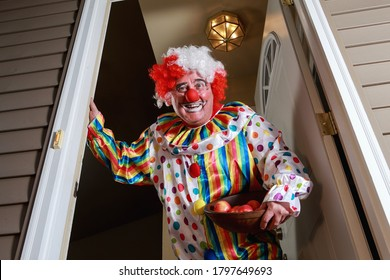 Awkward man dressed in a clown costume handing out apples for trick or treat