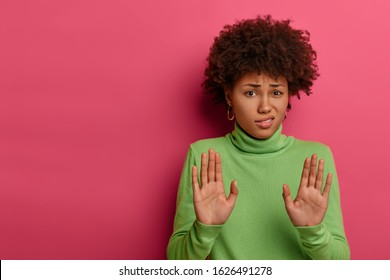 Awkward unimpressed woman with Afro hairstyle, pulls palms towards camera, refuses something, rejects proposal, wears green neck sweater, stands over crimson wall with empty space. No, thank you