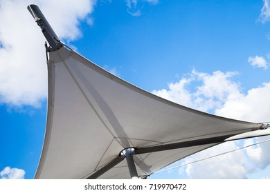 Awning in sail shape under cloudy sky background