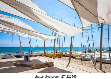 Awnings in sails shape covering relax area near sailing boats on the sandy beach in Calafell town, coast of Mediterranean sea, Catalonia, Spain