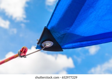 Awnings in sails shape over cloudy sky background. Detail of securing the tent from the sun to the cable