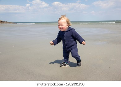 An awsome blond child running his first happy steps on the beach of the ocean during the sunny windy day with sand in his hands