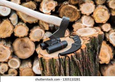 axe, binoculars and karambit knife case on the stump, firewoods on the background