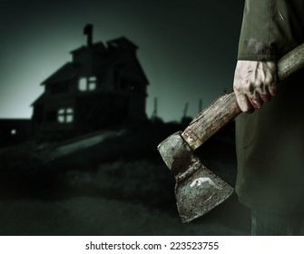 Axe with blood in male hand.  murderer or butcher looking on a night house, halloween theme