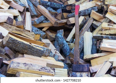 axe cleaver and a bunch of chopped beech, hornbeam and ash firewood for the stove and fireplace closeup