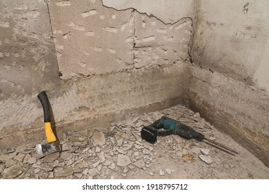 Axe and hammer dril are on the floor. Used for removing and knocking down old mouldy plaster. Home repair.