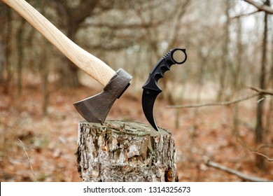 axe and karambit knife stuck in the stump in the forest