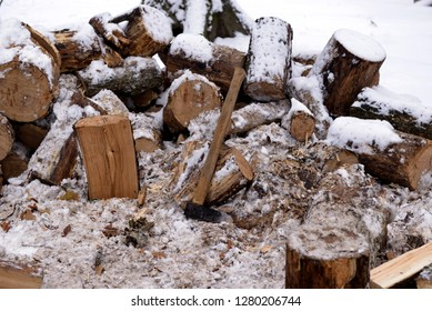 Axe on the background of firewood covered with snow. Firewood covered with snow,  background.