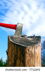 Axe in a splitting log against beautiful blue sky with fluffy clouds