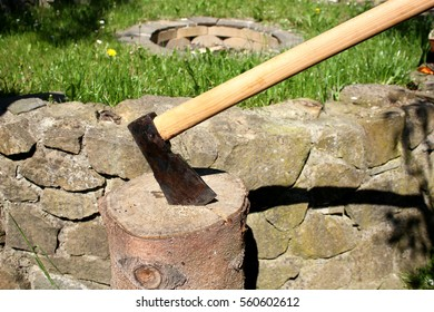 Axe stuck in the log, stone wall in the background